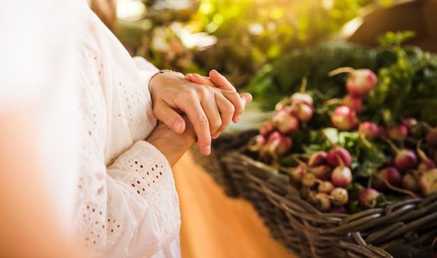 Mujer de pie delante de puesto de verduras en el mercado