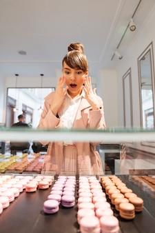 Mujer de pie delante de la vitrina de cristal con pasteles