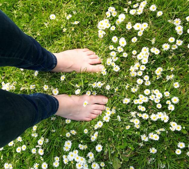 Mujer de pie descalzo en la hierba verde y flores blancas