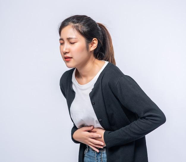 Una mujer de pie con dolor de estómago y presiona su mano sobre su estómago.