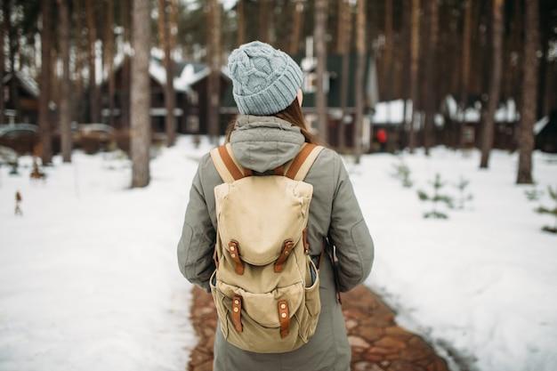 Mujer está de pie con la espalda en el bosque en el invierno