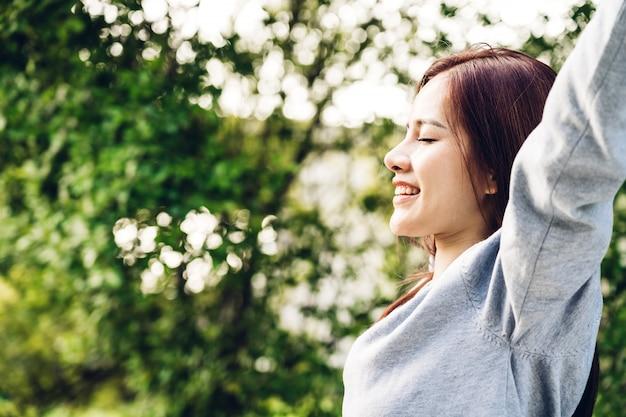 Mujer de pie estira sus brazos, relájate y disfruta con la naturaleza aire fresco