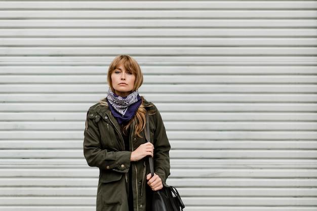 Mujer de pie frente a una tienda cerrada durante la pandemia de coronavirus