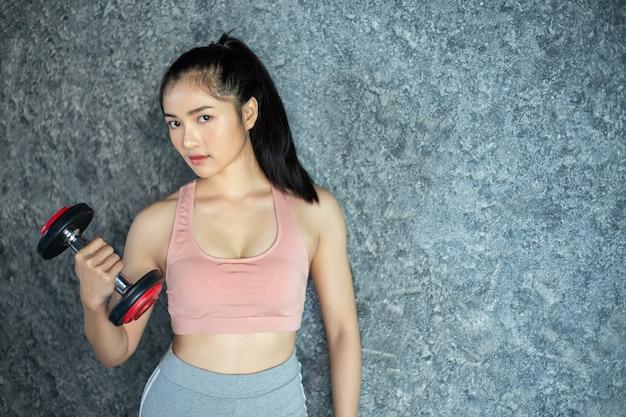 Mujer de pie haciendo ejercicio con una pesa roja en el gimnasio.