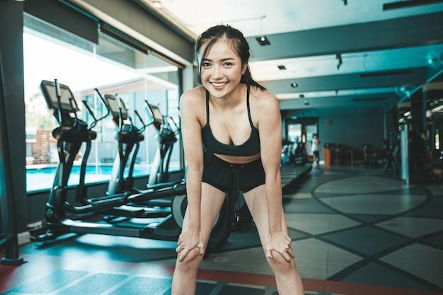 Mujer de pie se inclinó y la mano atrapa las rodillas antes de hacer ejercicio en el gimnasio.