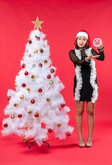 Una mujer está de pie junto al árbol de navidad.
