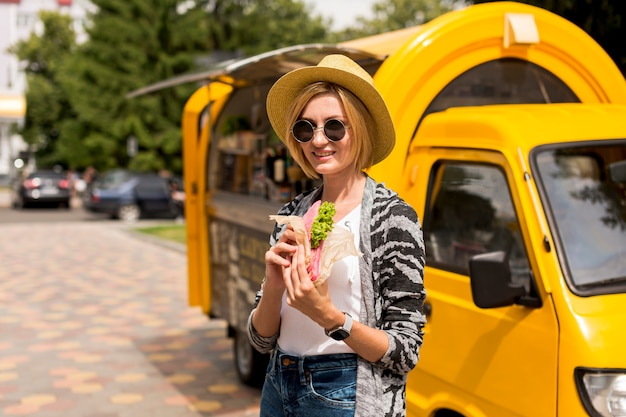 Mujer de pie junto al camión de comida