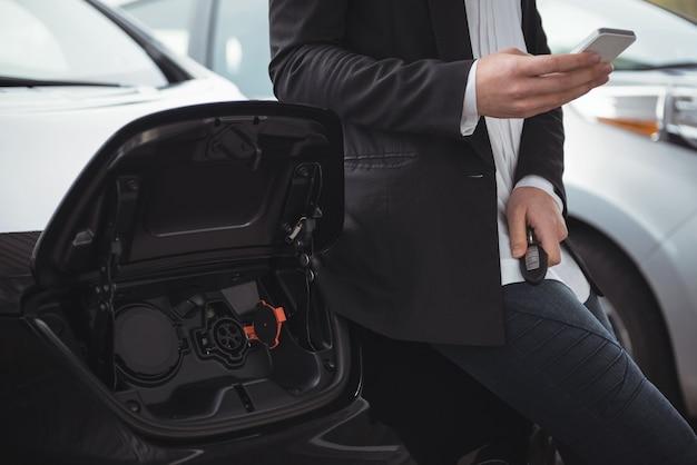 Mujer de pie junto al coche eléctrico y mediante teléfono móvil