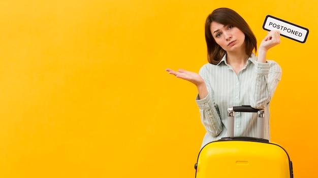 Mujer de pie junto a su equipaje mientras sostiene un cartel pospuesto con espacio de copia