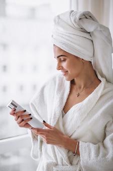 Mujer de pie junto a la ventana en bata de baño