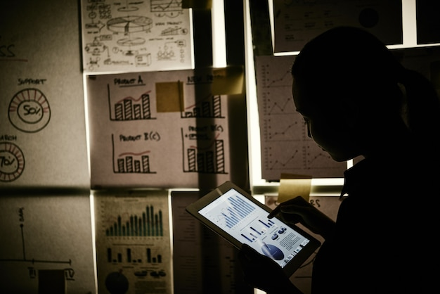 Mujer de pie junto a la ventana cubierta con gráficos de negocios y trabajando en tableta