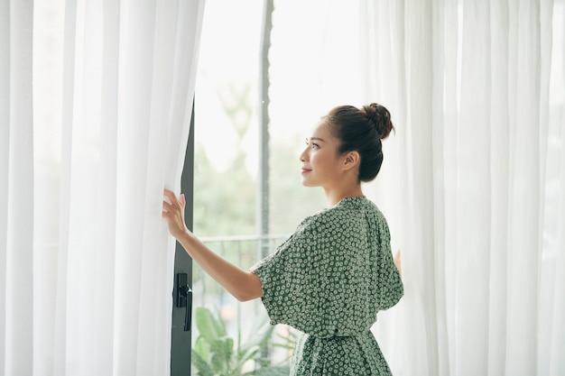 Mujer de pie junto a la ventana de la sala y cortinas de apertura