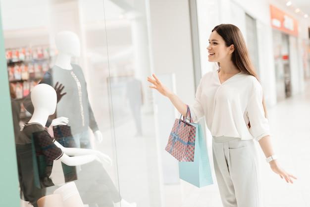 La mujer está de pie junto a la ventana de la tienda mirando el vestido nuevo.