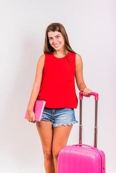 Mujer de pie con maleta rosa y sosteniendo el cuaderno