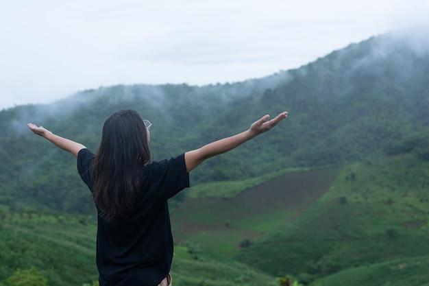 Una mujer de pie en medio de la montaña con una pose refrescante.