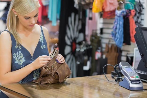 Mujer de pie en el mostrador mirando a través del bolso