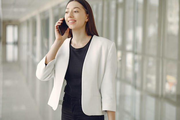 Mujer de pie en la oficina con un teléfono
