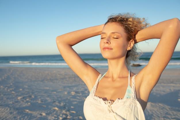 Mujer de pie con los ojos cerrados en la playa