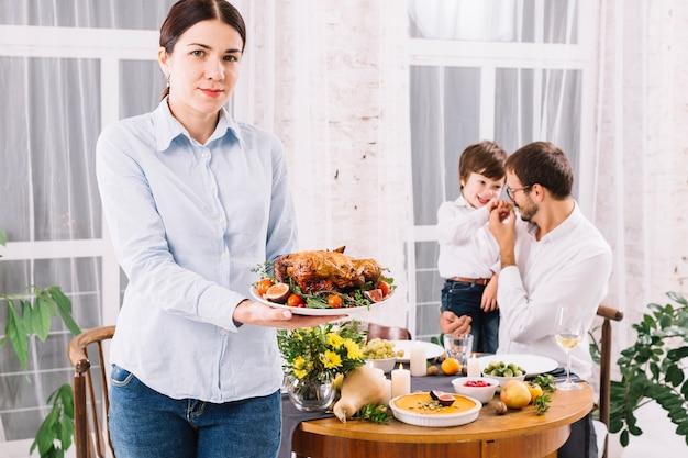 Mujer de pie con pollo al horno