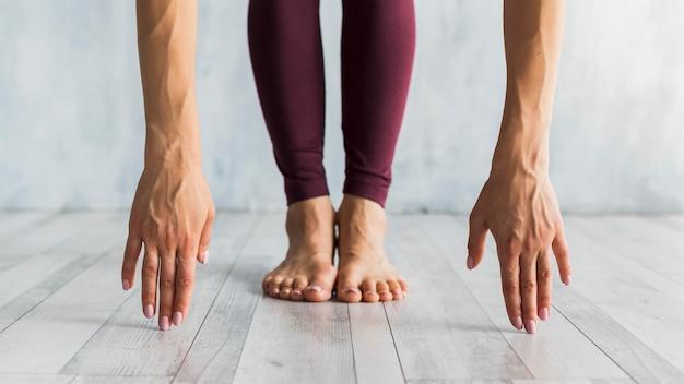 Mujer de pie en una pose de flexión hacia adelante