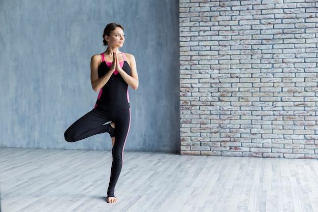 Mujer de pie en pose de yoga de árbol