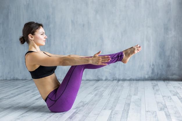 Mujer de pie en una pose de yoga de barco lleno