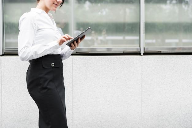 Mujer de pie de primer plano con tableta