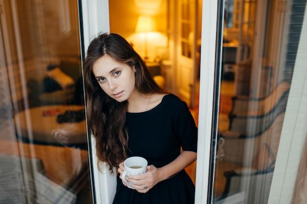 Mujer de pie en la puerta del balcón