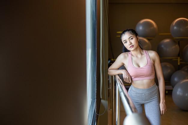 Una mujer de pie relajada, con las manos colocadas en un riel de acero en el gimnasio.