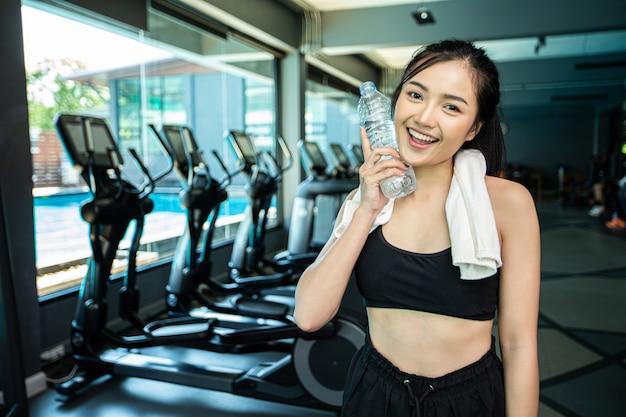 Mujer de pie y relajante después de hacer ejercicio, sosteniendo una botella de agua para tocar la cara.