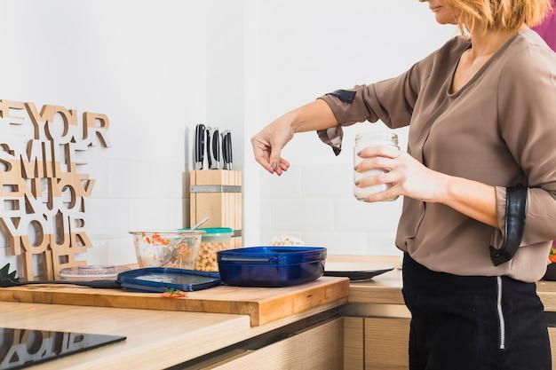 Mujer de pie en la sala de cocina de alimentos