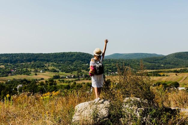 Mujer de pie sobre una roca y levantando una mano en el aire