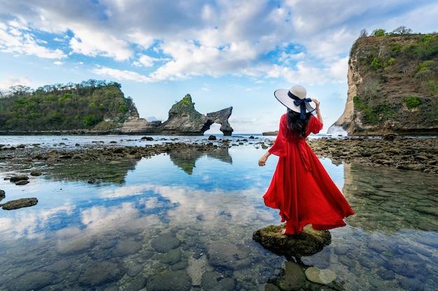 Mujer de pie sobre la roca en la playa atuh, isla de nusa penida en bali, indonesia