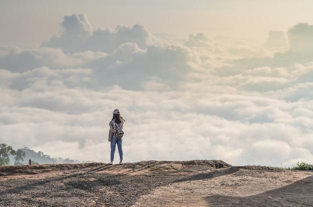 Mujer de pie solo en el acantilado sobre el paisaje de nubes y mirando en la niebla, travel lifestyl