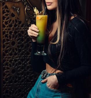 Mujer de pie y sosteniendo coloridos cócteles en el bar