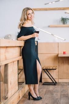 Mujer de pie y sosteniendo la copa de vino