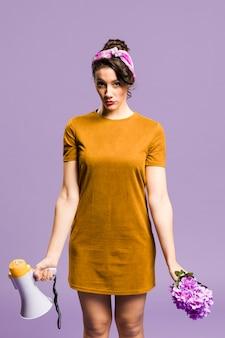 Mujer de pie y sosteniendo megáfono y vista frontal de flores