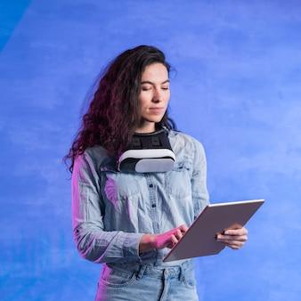 Mujer de pie y trabajando en su tableta
