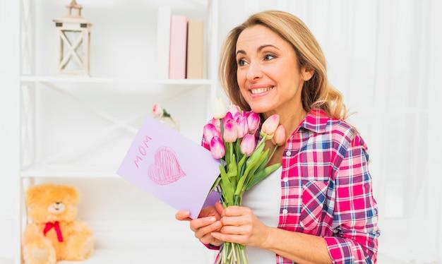 Mujer de pie con tulipanes y tarjeta de felicitación