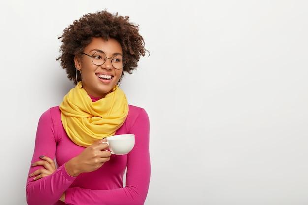 La mujer de piel oscura alegre y sonriente sostiene la taza con café aromático, usa lentes ópticos, bufanda amarilla y cuello alto rosa, aislado sobre fondo blanco.