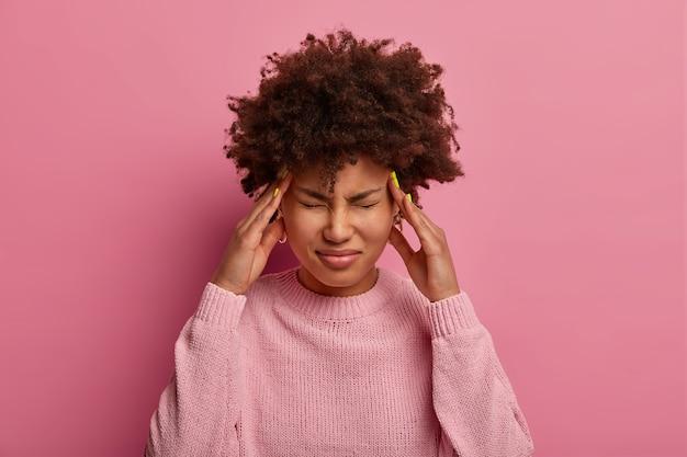 Mujer de piel oscura angustiada se frota las sienes, se siente mareada y dolor de cabeza severo
