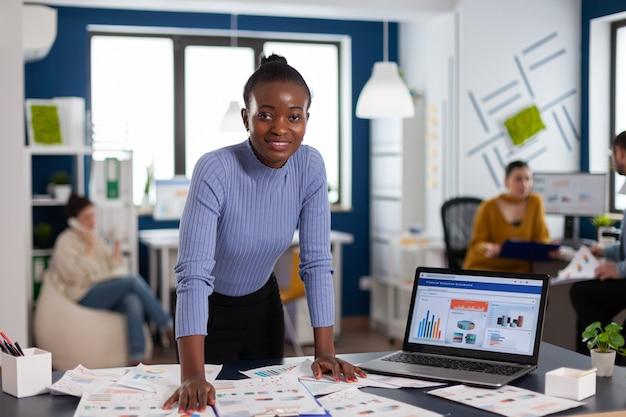 Mujer de piel oscura y colegas en la oficina de puesta en marcha corporativa trabajando para terminar el proyecto. equipo diverso de gente de negocios que analiza los informes financieros de la empresa desde la computadora.