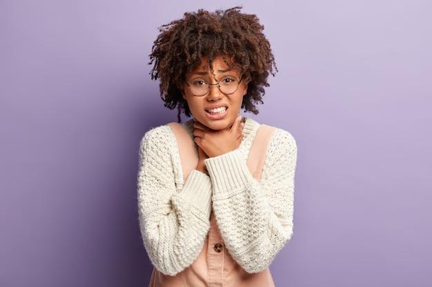 Mujer de piel oscura disgustada que sufre de asfixia, mantiene ambas manos en la garganta, aprieta los dientes, tiene el pelo afro rizado