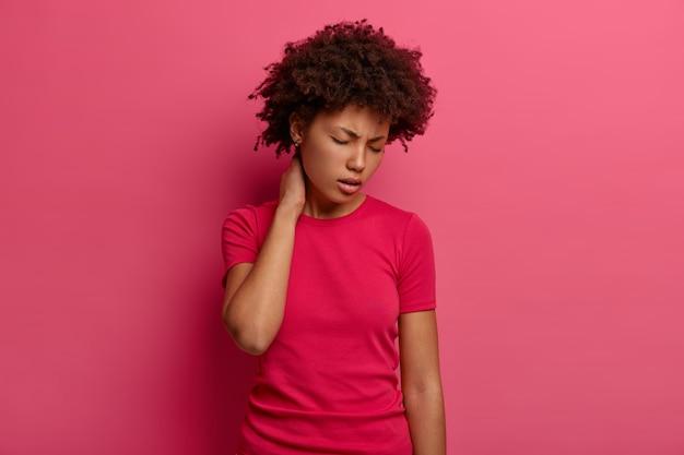 Mujer de piel oscura disgustada toca el cuello, siente dolor en la espalda después de caer de las escaleras, sufre de sensaciones dolorosas en la columna, inclina la cabeza y cierra los ojos, usa una camiseta informal, aislada en una pared rosa
