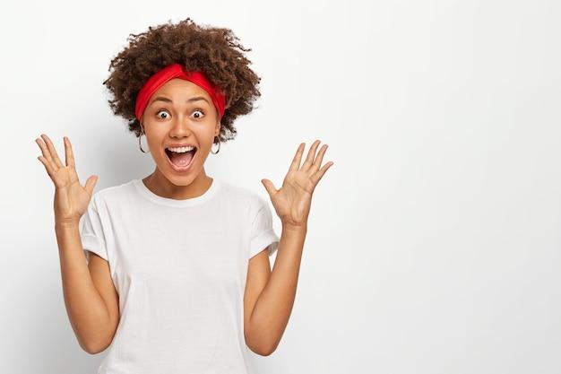 Mujer de piel oscura exagerada que levanta las palmas de las manos, mantiene la boca bien abierta, reacciona ante algo increíble, vestida con ropa casual