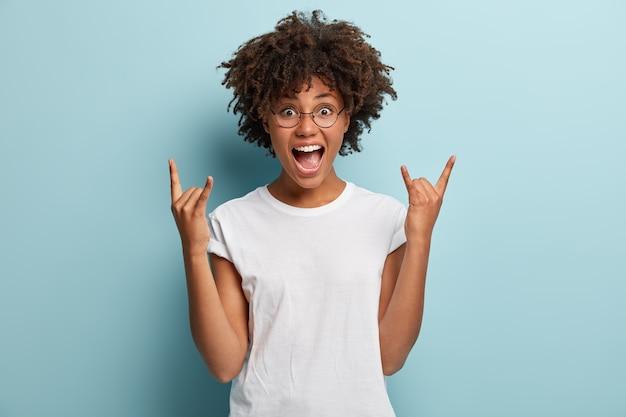 Mujer de piel oscura grita de felicidad, tiene la boca muy abierta, hace un gesto de rock n roll, usa un atuendo informal
