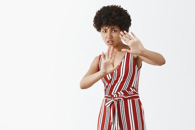 Mujer de piel oscura insegura, disgustada e infeliz con peinado afro en traje de moda levantando las palmas en gesto de protección, preocupado por derramar bebida en la ropa, frunciendo el ceño