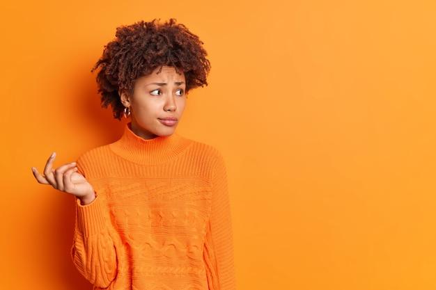 Mujer de piel oscura insegura con problemas con el pelo rizado levanta la mano intenta resolver el problema parece perplejo enfocado en la distancia