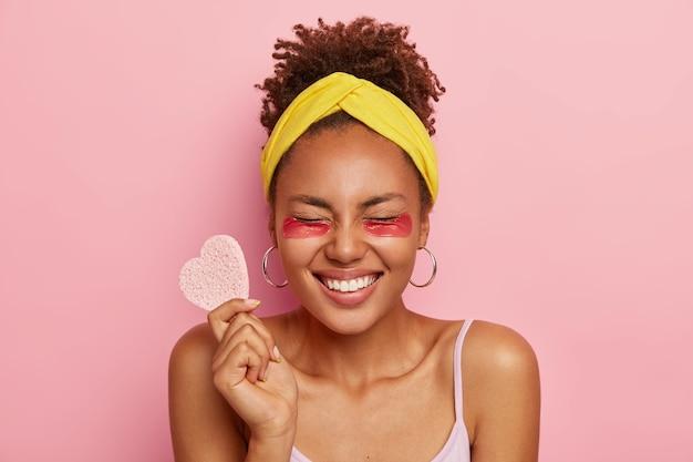 Una mujer de piel oscura llena de alegría cierra los ojos, usa parches faciales debajo de los ojos, se siente aliviada y satisfecha, sostiene una esponja cosmética en forma de corazón, modela contra la pared rosa. belleza natural