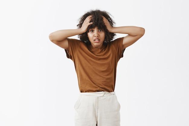 Mujer de piel oscura molesta y preocupada, comenzando el pánico tomándose las manos en la cabeza y frunciendo el ceño infeliz